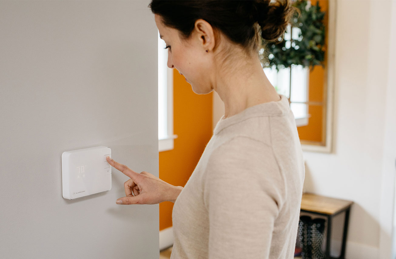 woman touching thermostat
